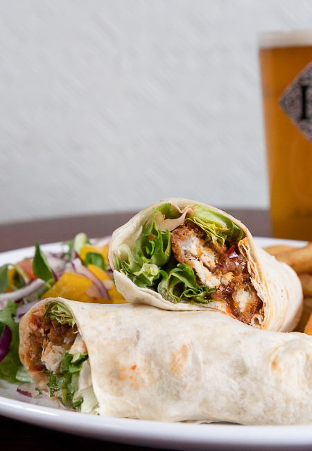 Southern fried chicken wrap served with salad and chips